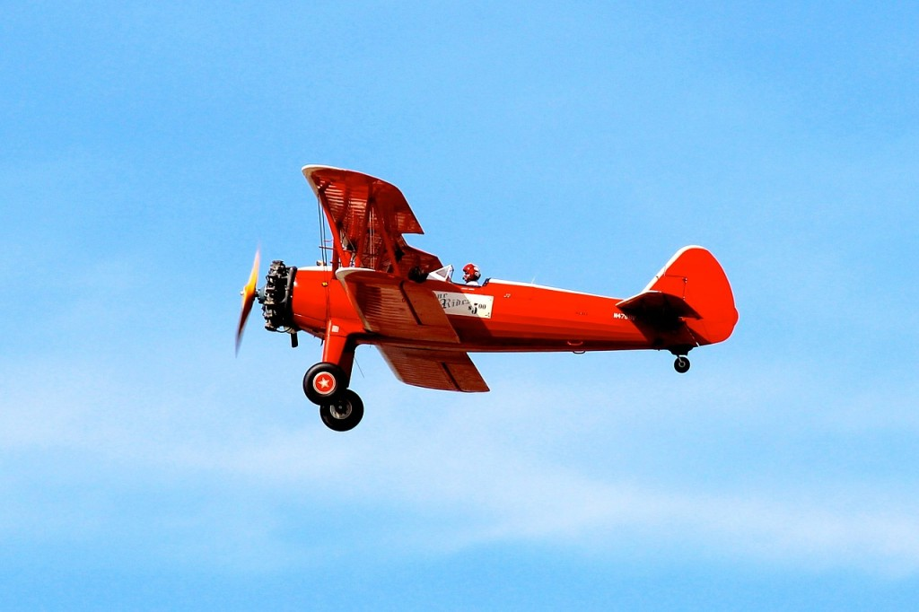 red biplane flying over blue skies