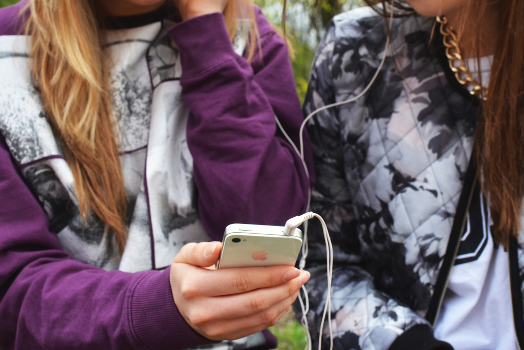 Two young women listening to music on an iPhone together