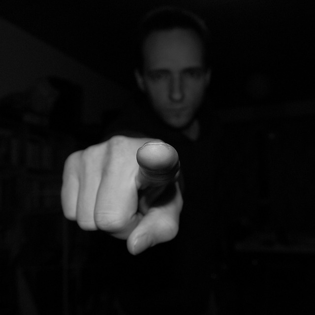 black and white photo of man pointing finger at reader
